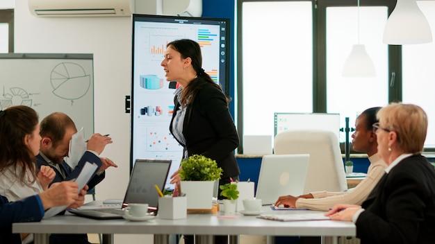 Mujer de negocios enojada gritando a diversos colegas durante la reunión de la oficina tirando documentos, en desacuerdo sobre un mal contrato comercial. grupo multirracial joven de personas que trabajan en la sala de juntas.