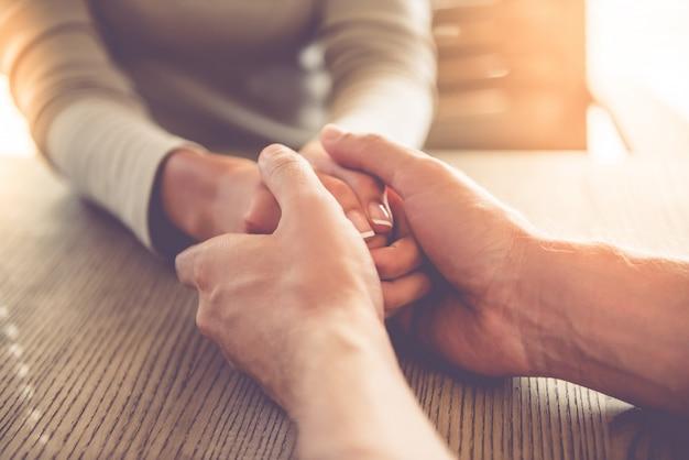Mujer de negocios entrelazando las manos y el hombre la calma