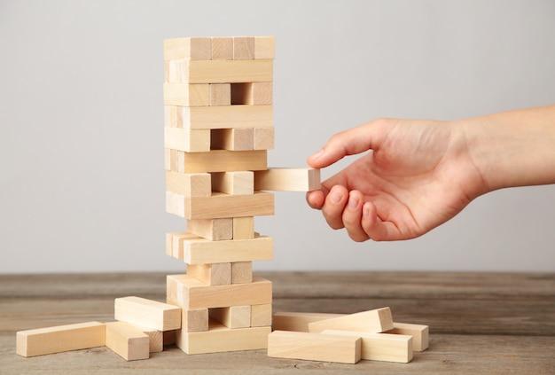 La mujer de negocios escoge y pone a mano el último bloque del rompecabezas de madera. bloque de madera en pared gris