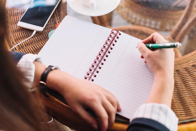 Mujer de negocios escribiendo en cafetería