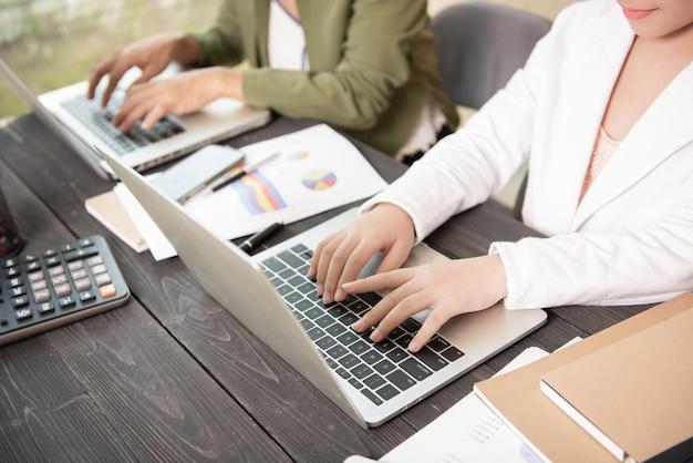 Mujer de negocios escribiendo en la computadora portátil en el lugar de trabajo mujeres que trabajan en el teclado de la mano de la oficina en casa.