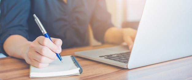 La mujer de negocios está escribiendo en un cuaderno con una pluma y está usando una computadora portátil para trabajar en la oficina.