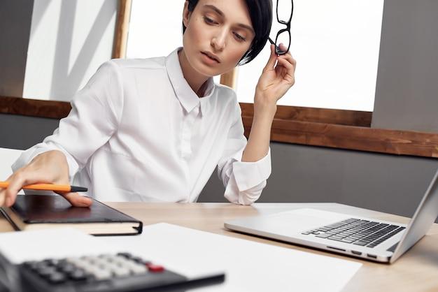 Mujer de negocios, en el escritorio, con, anteojos, autoconfianza, fondo claro