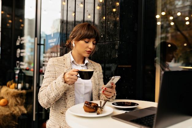 Mujer de negocios con estilo joven en serio en chaqueta con teléfono inteligente y trabajando en la computadora portátil, escuchando música y tomando café