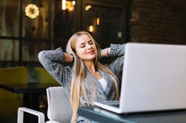 Mujer de negocios de estilo con portátil en cafetería agradable