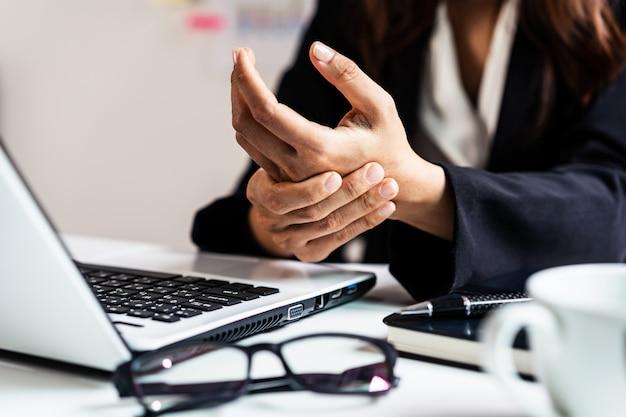 Mujer de negocios estresada que sufre de dolor en la muñeca, concepto de síndrome de office
