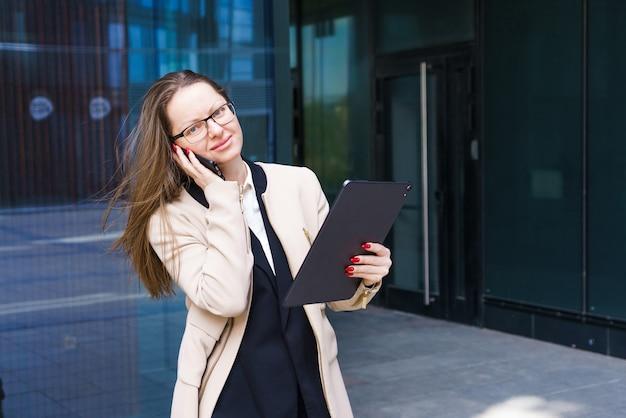 Mujer de negocios de etnia caucásica con gafas hablando por teléfono cerca del centro de negocios en ...
