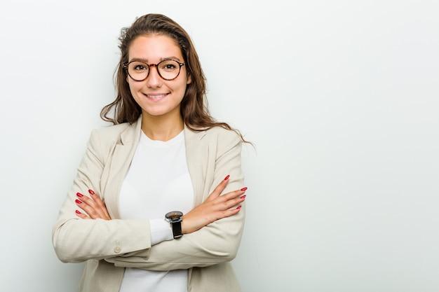 Mujer de negocios europea joven que se siente segura, cruzando los brazos con determinación.