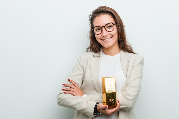 Mujer de negocios europea joven que sostiene una lingote de oro que sonríe confiada con los brazos cruzados.