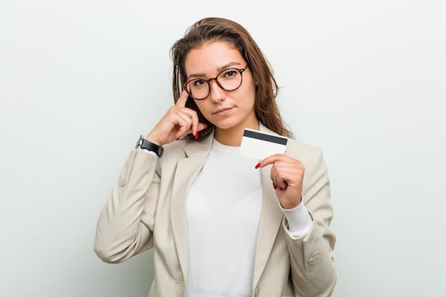 Mujer de negocios europea joven que sostiene una tarjeta de crédito que señala su templo con el dedo, pensando, centrado en una tarea.