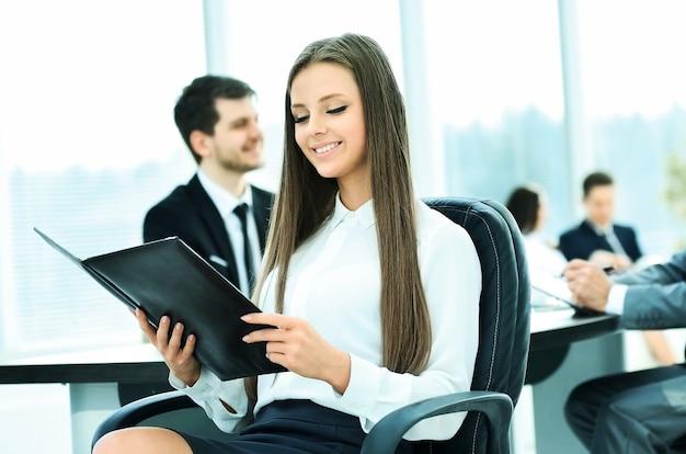 Mujer de negocios exitosa estudiando un plan de trabajo de negocios en la oficina en el fondo del trabajo de su equipo