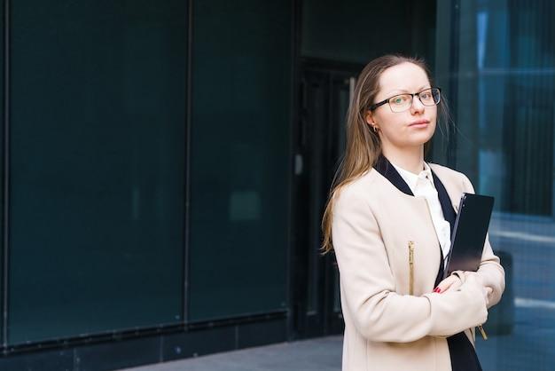 Una mujer de negocios exitosa de etnia caucásica con una carpeta de papeles en la mano en un abrigo y ...