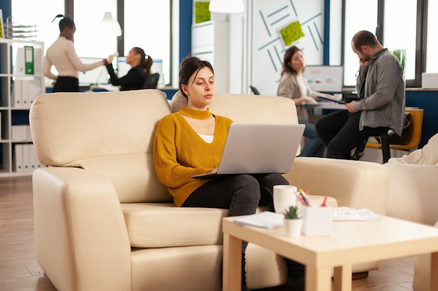 Mujer de negocios exitosa que trabaja en la computadora portátil en el proyecto de puesta en marcha sentado en un sofá acogedor
