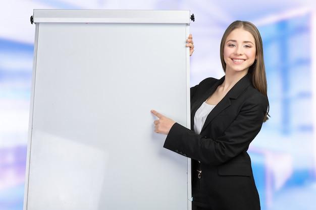 La mujer de negocios explica en la pizarra