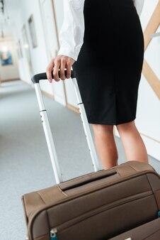 Mujer de negocios en falda caminando con su maleta
