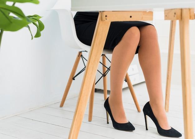 Mujer de negocios en la falda que se sienta en la tabla en oficina