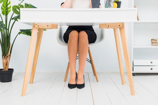 Mujer de negocios en la falda que se sienta en la tabla