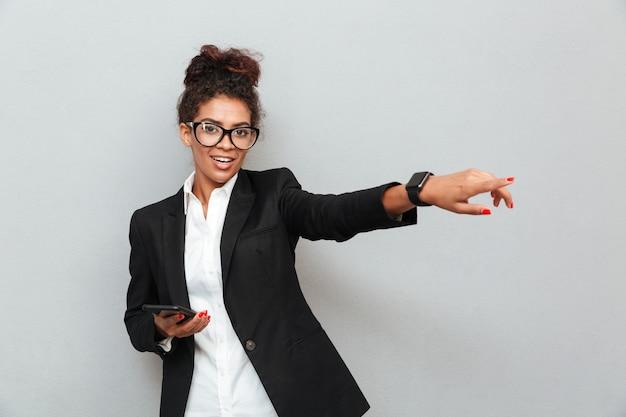 Mujer de negocios feliz africana sobre pared gris