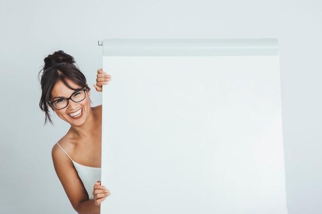 Mujer de negocios feliz escondida detrás de la pizarra blanca