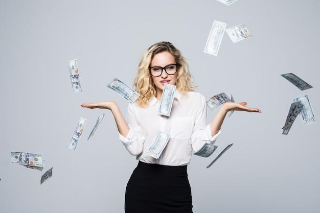 Mujer de negocios feliz bajo una lluvia de dinero hecha de dólares aislado en la pared blanca