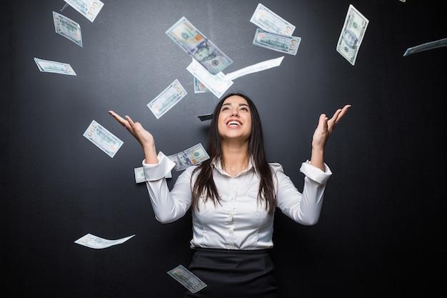 Mujer de negocios feliz bajo una lluvia de dinero hecha de dólares aislado en la pared negra