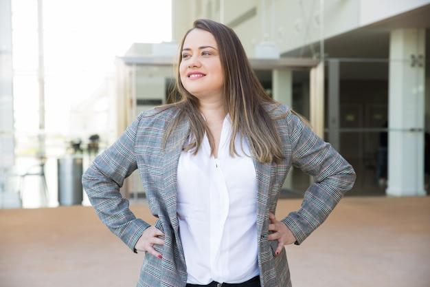 Mujer de negocios feliz manteniendo las manos en las caderas al aire libre