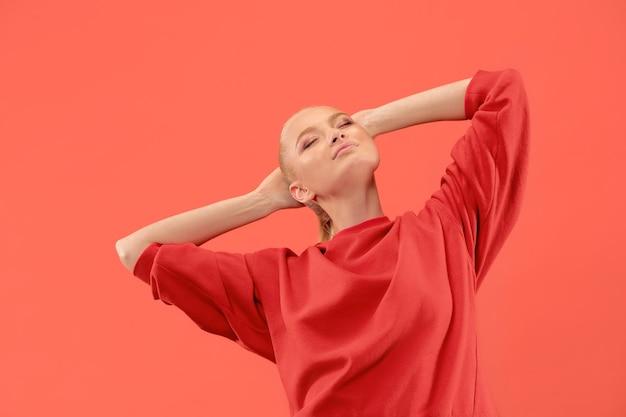 Mujer de negocios feliz de pie, sonriendo aislado sobre fondo de estudio de coral de moda. hermoso retrato femenino de medio cuerpo. los jóvenes satisfacen a la mujer. las emociones humanas, el concepto de expresión facial.