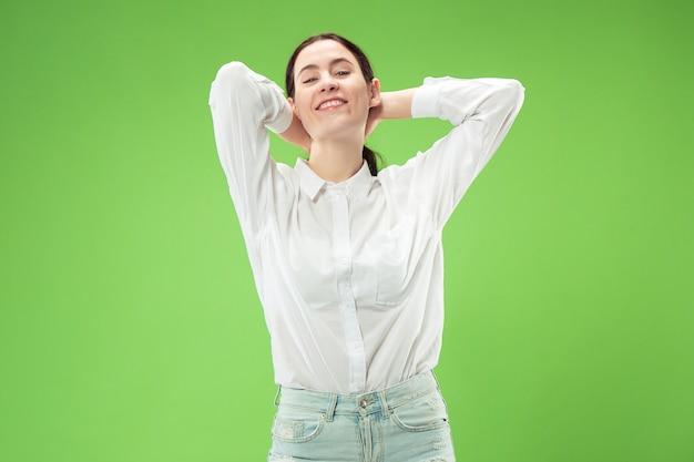 Mujer de negocios feliz de pie y sonriendo aislado sobre fondo verde de estudio. hermoso retrato femenino de medio cuerpo. joven mujer emocional. las emociones humanas, el concepto de expresión facial.