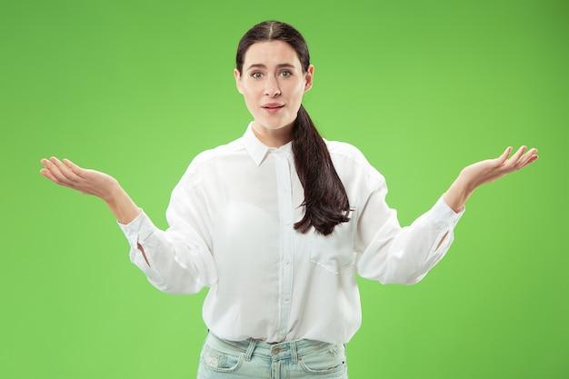 Mujer de negocios feliz de pie y sonriendo aislado sobre fondo verde de estudio.