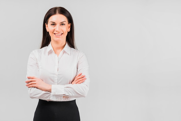 Mujer de negocios feliz que se coloca con los brazos cruzados