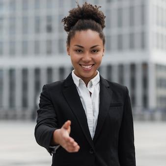 Mujer de negocios feliz que muestra la mano