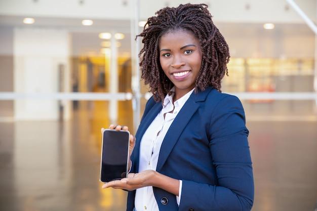 Mujer de negocios feliz que presenta en la pantalla del celular