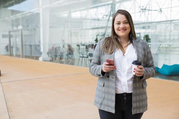 Mujer de negocios feliz que sostiene smartphone y la bebida al aire libre