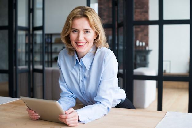 Mujer de negocios feliz que usa la tableta en la mesa