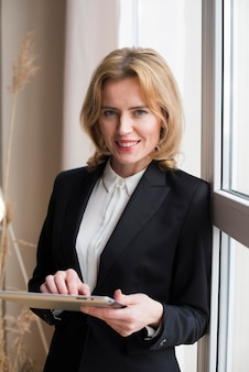 Mujer de negocios feliz que usa la tableta