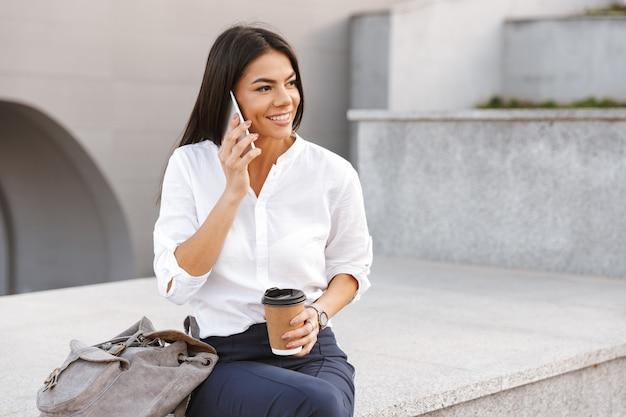 Mujer de negocios feliz sentado al aire libre con una taza de café