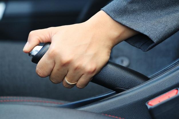Mujer de negocios el freno de mano del coche.