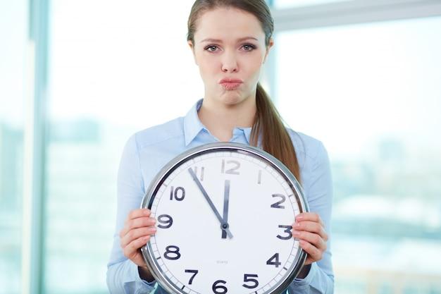 Mujer de negocios frustrada sosteniendo un reloj grande