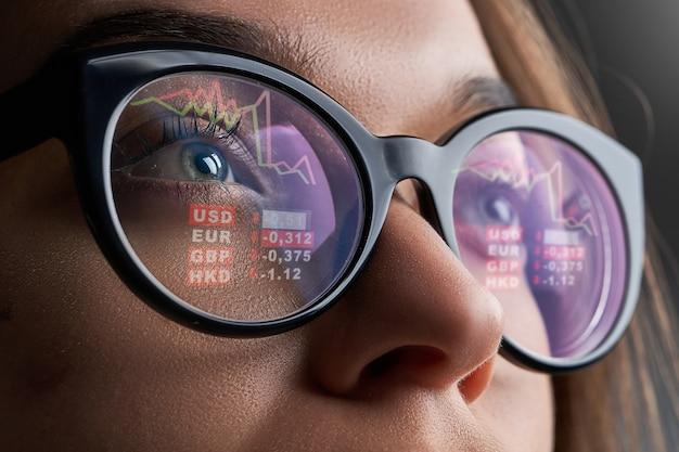 Mujer de negocios con gafas mira cotizaciones bursátiles y tipos de cambio durante la crisis financiera