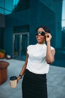 Mujer de negocios en gafas de sol con café descansando