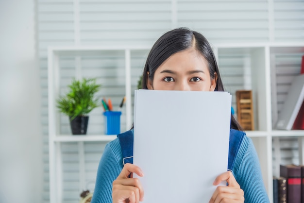 Mujer de negocios con gastos de casa de papel sintiéndose feliz, trabajando sola en la habitación, ella es de pelo negro.