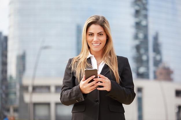 Mujer de negocios hablando al móvil en entorno urbano