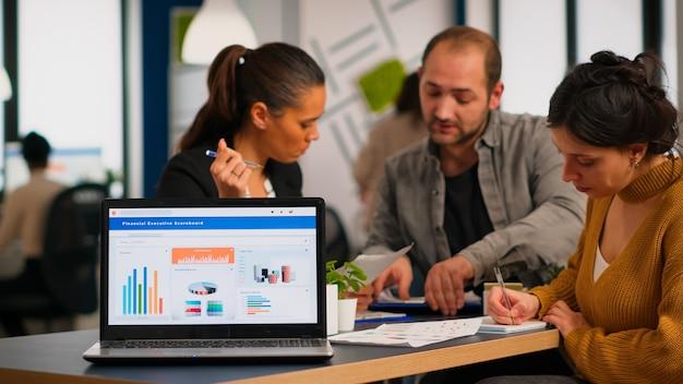 Mujer de negocios hablando de proyecto financiero, tomando notas, discutiendo ideas de puesta en marcha usando laptop. diversos empleados reunidos en co-working, proceso de trabajo en empresa ocupada, concepto de ayuda de trabajo en equipo