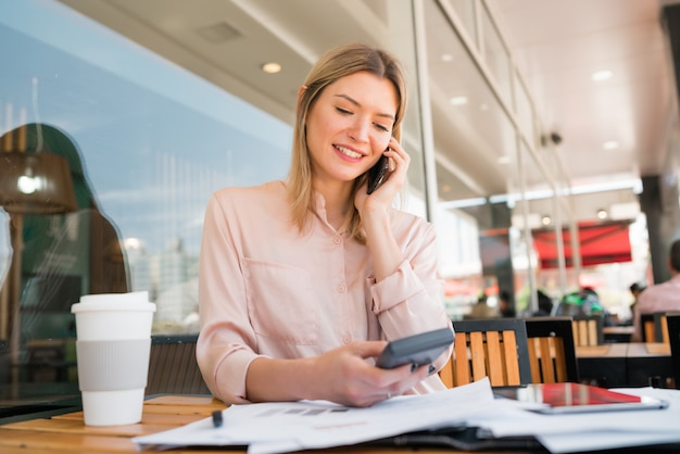 Mujer de negocios hablando por teléfono mientras trabajaba en la cafetería.