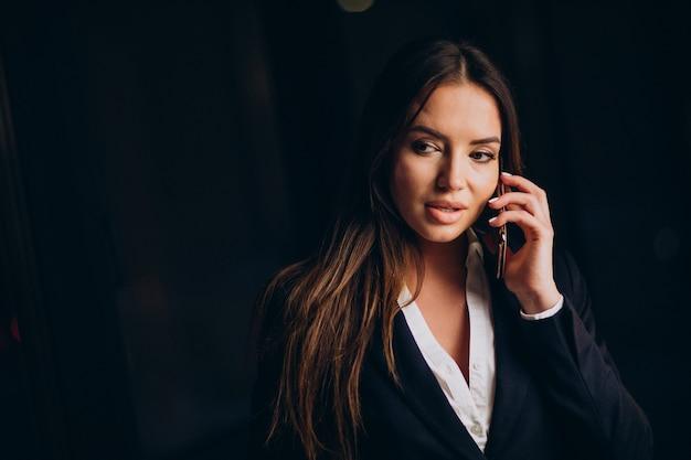 Mujer de negocios hablando por teléfono y quedarse hasta altas horas de la noche en la oficina