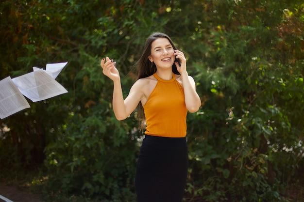 Mujer de negocios hablando por teléfono y tirando papel de sus manos. el camino al trabajo, caminar por el parque.