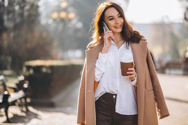 Mujer de negocios hablando por teléfono y tomando café