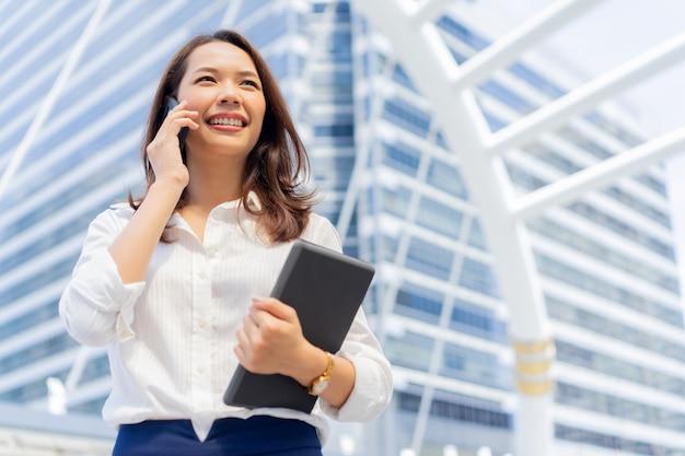 Mujer de negocios hablar con el cliente en el fondo exterior de la ciudad por concepto de negocio