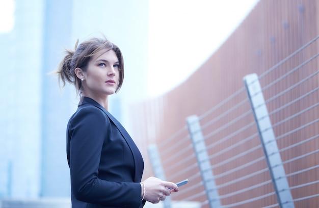 Mujer de negocios, hablar, móvil, en, ambiente urbano