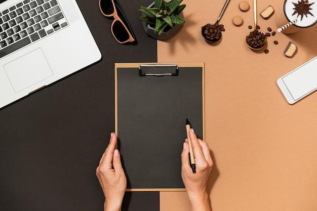 La mujer de negocios hace el papeleo, sujeta el portapapeles y la pluma sobre la vista superior del diseño del café del espacio de trabajo de moda. diseño de papel en blanco, portátil, papelería sobre mesa.
